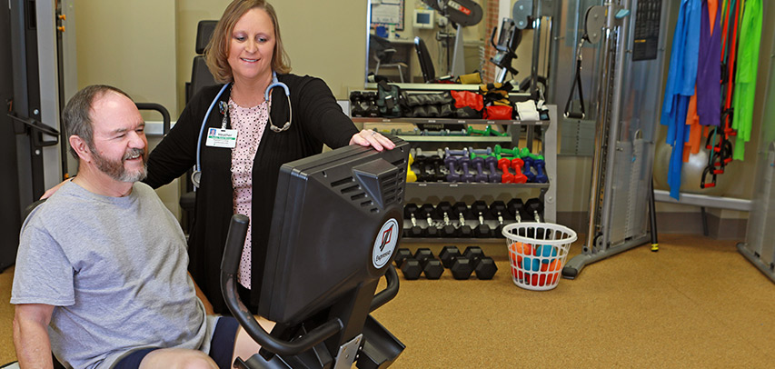 A physical therapist adjusts the settings on screen for a patient seated on an exercise bike in the Wellness Center.