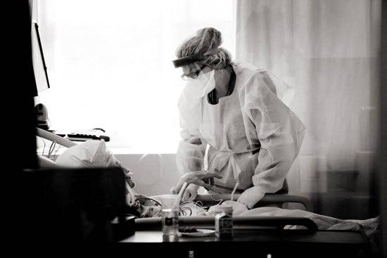 A care provider in full PPE and face shield standing beside an elderly patient's bed, leaning in to listen, with medical equipment silhouetted in the foreground.