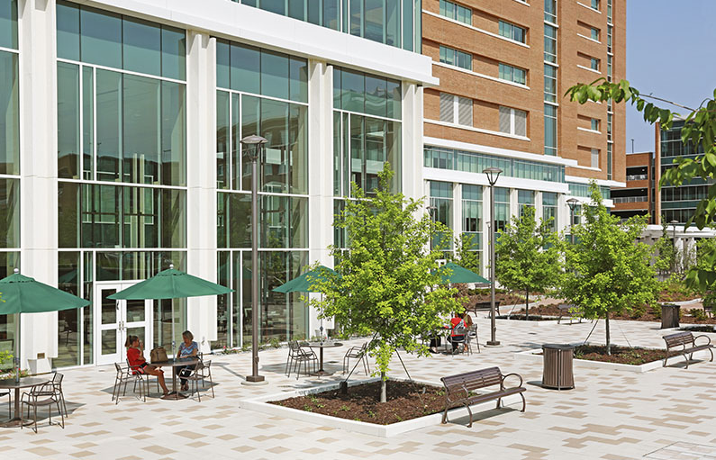 The courtyard outside the new LMC tower, landscaped with brick and trees, full of patio tables and chairs under green umbrellas.