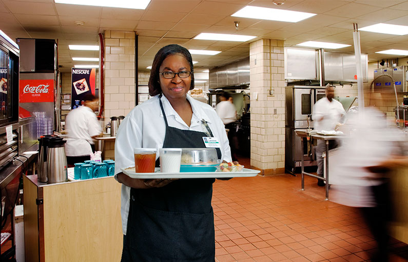 A smiling food service employee in an apron and hair net, holding a tray of food in the middle of the large hospital cafeteria kitchen.