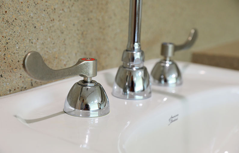 Close-up of copper-coated faucet handles next to a sparkling clean sink.
