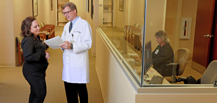 An LMC doctor and nurse standing in a warm doctor's office hallway lined with chairs and art, looking over paperwork together.