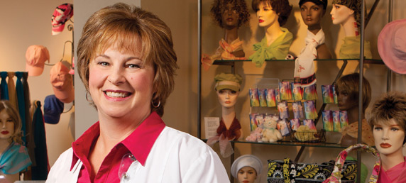 LMC nurse navigator Kelly Jeffcoat smiling inside of Becky's Place Boutique, a hospital-run boutique for women recovering from cancer and needing wigs, hats, scarves and more, which can be seen in the background.